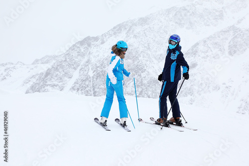 Woman and man skiers in suits and helmets turn at winter