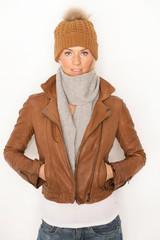 Junge Blondine mit Lederjacke und Wollmütze