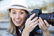 Beautiful woman photographer holding photo camera