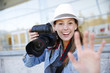 Cheerful photographer showing hand towards camera