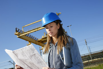 Woman engineer reading construction plan on site