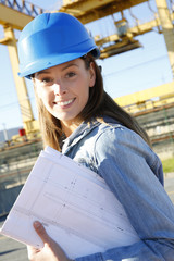Woman engineer standing on construction site with plan