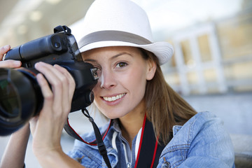 Portrait of smiling girl holding photo camera