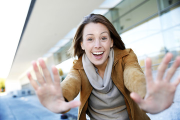 Cheerful girl showing hands towards camera