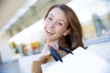 Cheerful girl in town holding shopping bags