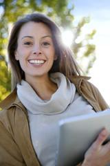 Beautiful girl using digital tablet outside