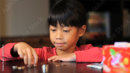 Happy Six Year Old Asian Girl Counting Money