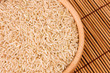 Raw brown rice in wooden bowl on bamboo close-up