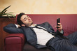 Portrait of tired young businessman typing on cellphone on sofa.