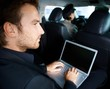 Young man working on laptop in limousine