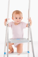 Beautiful baby girl climbing on ladder