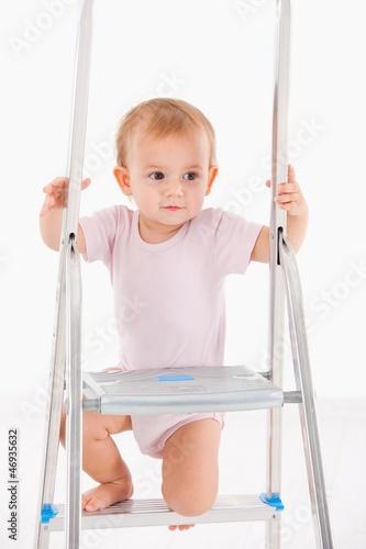 Beautiful baby girl climbing on ladder