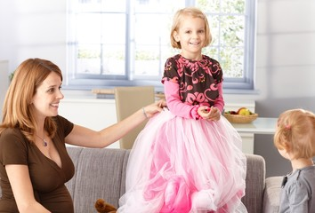 Happy little girl in princess skirt at home