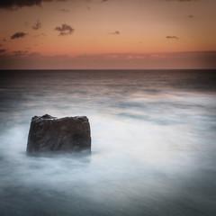 Roca en el mar al atardecer