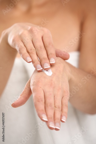 Close up of woman applying cream on her hand