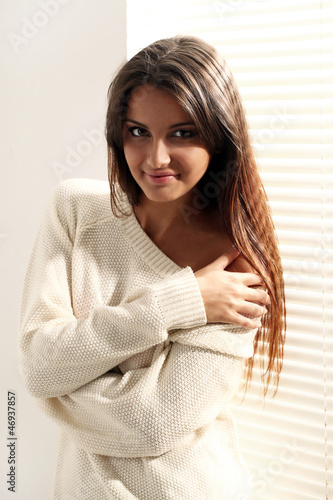 Portrait of young woman in white sweater