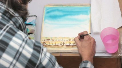 artist working on a landscape watercolor
