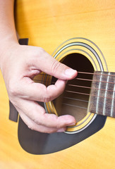 Close up of hand playing acoustic guitar.