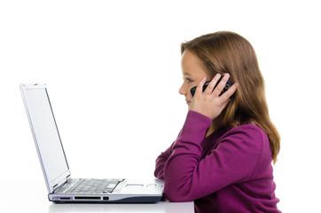 kind telefoniert und spielt am laptop