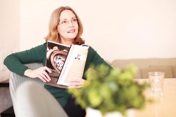 Schöne ältere Dame ließt eine Zeitschrift