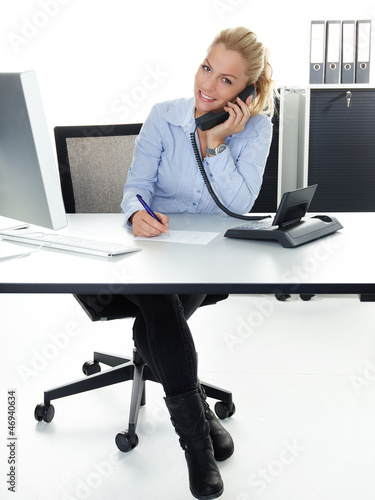 Pretty secretary makes notes while having a call at work