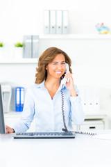 geschäftsfrau am telefon zwinkert mit dem auge