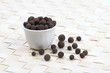Allspice berries in a white pot