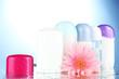deodorant botttles with flower on blue background