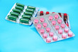 Capsules and pills packed in blisters, on blue background
