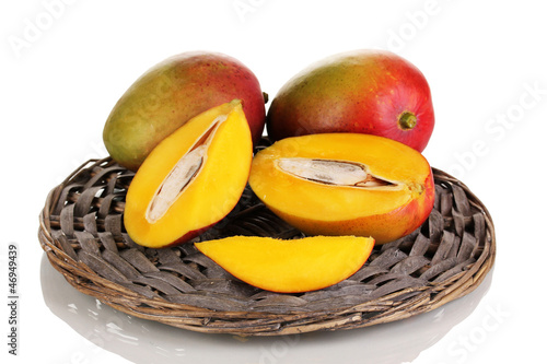 Ripe appetizing mango on wicker cradle isolated on white