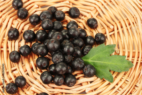 chokeberry with green leaf on wicker mat close-up
