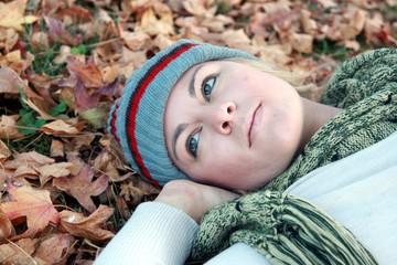 ritratto di ragazza distesa sulle foglie d'autunno