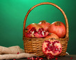 Ripe pomegranates on basket on wooden table on green background