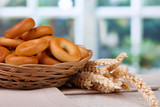 tasty bagels in basket and spikelets on table