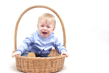 Baby boy crying in basket on white background