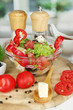 Fresh greek salad in glass bowl surrounded by ingredients for