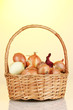 Ripe onions in basket on yellow background