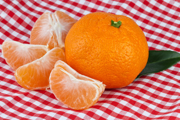 tangerines on red-white tablecloth