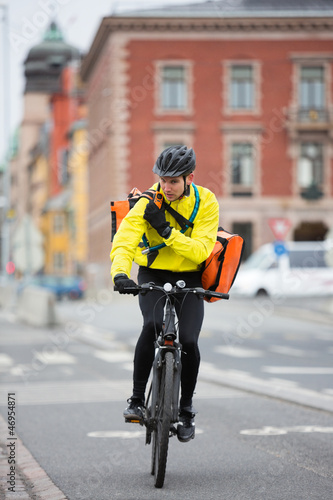 Cyclist With Courier Bag Using Walkie-Talkie