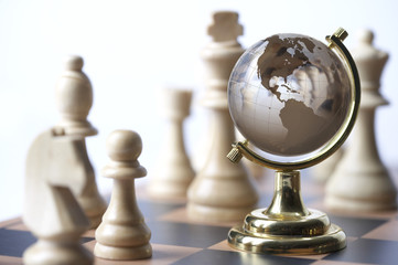 Chessboard with chess pieces and globe
