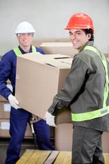 Foremen Lifting Cardboard Box in Warehouse