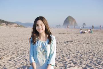 Beautiful biracial girl on sandy beach near Haystack Rock