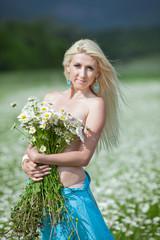 Attractive blonde in chamomile field