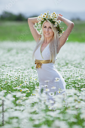 Attractive blonde in chamomile field.