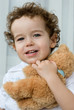 Curly-haired boy with a teddy bear