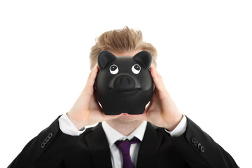 Businessman holding a piggybank in front of face