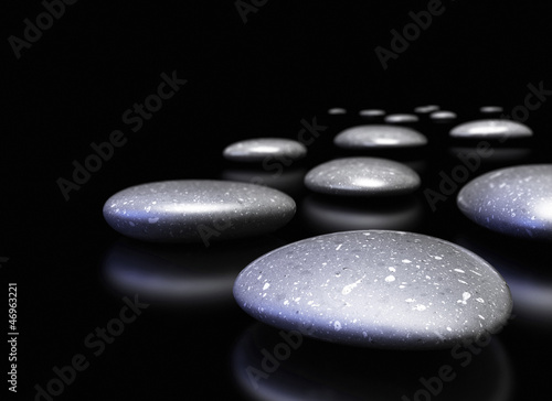 many pebbles in a row over black background