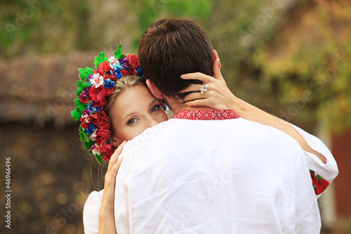 Young couple in Ukrainian national costumes hugging tenderly