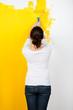 frau streicht die wohnung gelb