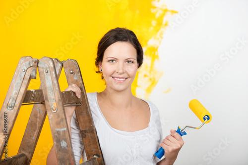 lächelnde frau renoviert die wohnung